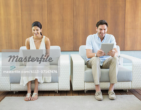 Couple using laptop and digital tablet in armchairs Stock Photo - Premium Royalty-Free, Image code: 6113-07147476