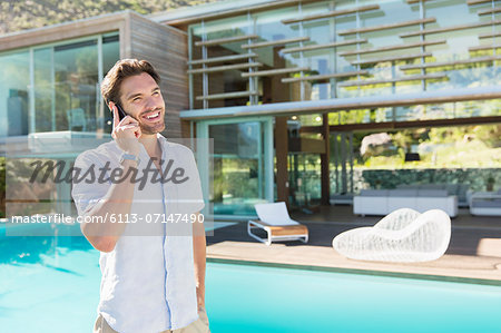 Man talking on cell phone at poolside Stock Photo - Premium Royalty-Free, Image code: 6113-07147490