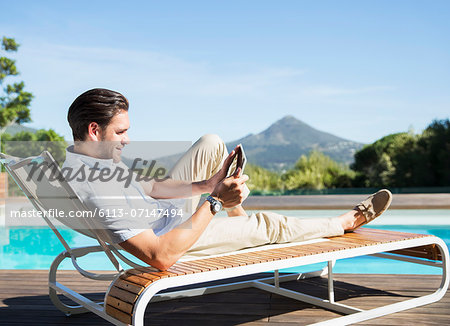 Man using digital tablet on lounge chair at poolside Stock Photo - Premium Royalty-Free, Image code: 6113-07147494