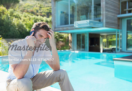 Man talking on cell phone at poolside Stock Photo - Premium Royalty-Free, Image code: 6113-07147497