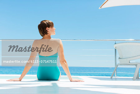 Woman relaxing poolside with ocean in background Stock Photo - Premium Royalty-Free, Image code: 6113-07147511