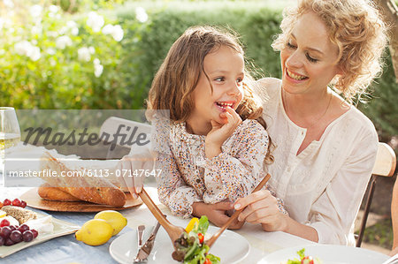 Mother and daughter eating in garden Stock Photo - Premium Royalty-Free, Image code: 6113-07147647