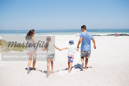 Family holding hands and walking on beach Stock Photo - Premium Royalty-Free, Image code: 6113-07147694