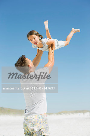 Father lifting daughter overhead on beach Stock Photo - Premium Royalty-Free, Image code: 6113-07147697