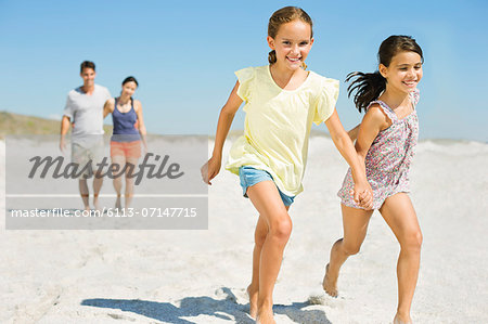 Girls holding hands and running on beach Stock Photo - Premium Royalty-Free, Image code: 6113-07147715