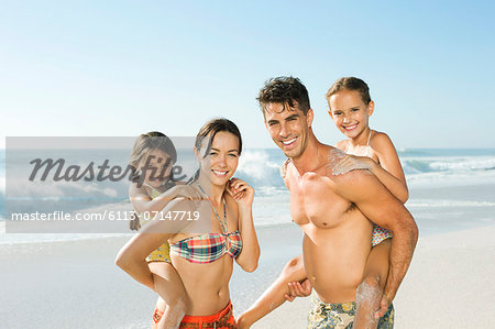 Parents carrying daughters piggyback on beach Stock Photo - Premium Royalty-Free, Image code: 6113-07147719