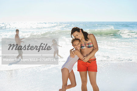 Mother and daughter hugging on beach Stock Photo - Premium Royalty-Free, Image code: 6113-07147726