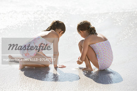 Girls playing together in surf on beach Stock Photo - Premium Royalty-Free, Image code: 6113-07147727