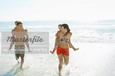 Parents carrying daughters piggyback in surf at beach Stock Photo - Premium Royalty-Free, Image code: 6113-07147728