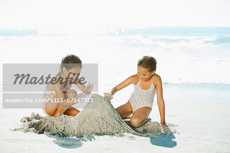 Girls building sandcastle on beach Stock Photo - Premium Royalty-Free, Image code: 6113-07147733
