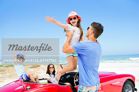 Father lifting daughter from convertible at beach Stock Photo - Premium Royalty-Free, Image code: 6113-07147762