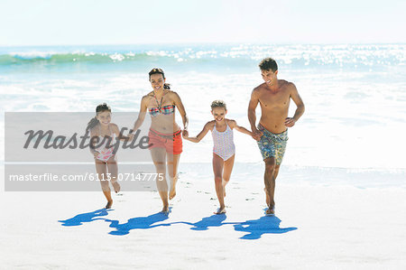 Family holding hands and running on beach Stock Photo - Premium Royalty-Free, Image code: 6113-07147775