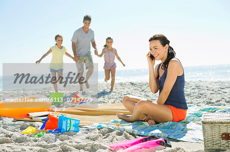 Woman talking on cell phone at beach Stock Photo - Premium Royalty-Free, Image code: 6113-07147779
