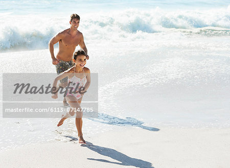 Father and daughter running in surf at beach Stock Photo - Premium Royalty-Free, Image code: 6113-07147785