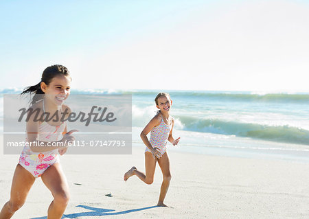 Girls running on beach Stock Photo - Premium Royalty-Free, Image code: 6113-07147793