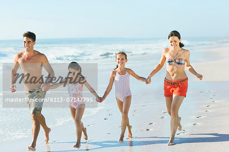 Family holding hands and running on beach Stock Photo - Premium Royalty-Free, Image code: 6113-07147795
