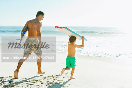 Father and son carrying surfboard and bodyboard on beach Stock Photo - Premium Royalty-Free, Image code: 6113-07147803
