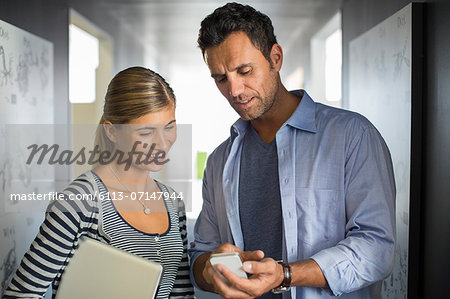 Business people looking down at cell phone in corridor Stock Photo - Premium Royalty-Free, Image code: 6113-07147944