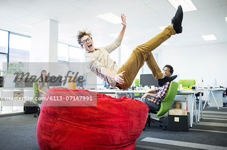 Businessman jumping into beanbag chair in office Stock Photo - Premium Royalty-Free, Image code: 6113-07147991