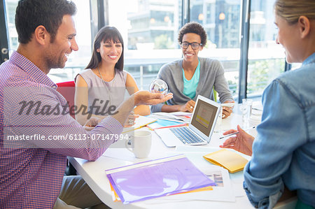 Business people examining ball in office Stock Photo - Premium Royalty-Free, Image code: 6113-07147994