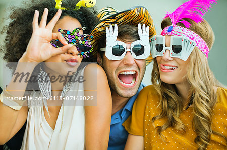 Smiling friends wearing decorative glasses Stock Photo - Premium Royalty-Free, Image code: 6113-07148022
