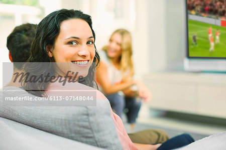Portrait of smiling woman on sofa Stock Photo - Premium Royalty-Free, Image code: 6113-07148044