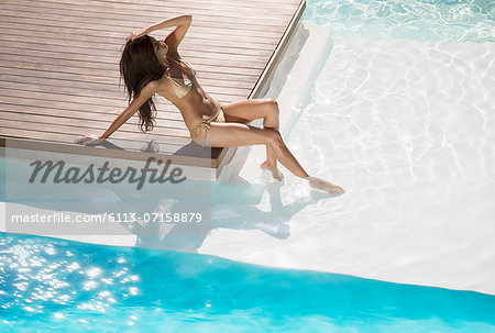 Woman relaxing at swimming pool Stock Photo - Premium Royalty-Free, Image code: 6113-07158879