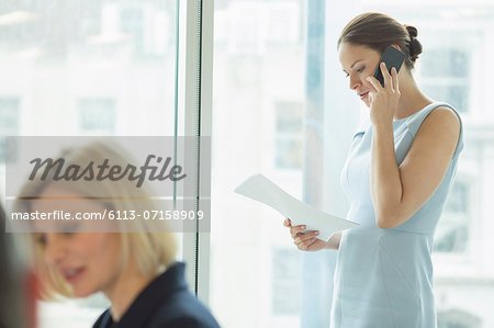 Businesswoman talking on cell phone in office Stock Photo - Premium Royalty-Free, Image code: 6113-07158909