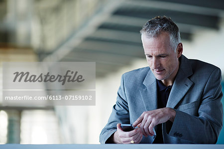 Businessman using cell phone Stock Photo - Premium Royalty-Free, Image code: 6113-07159102
