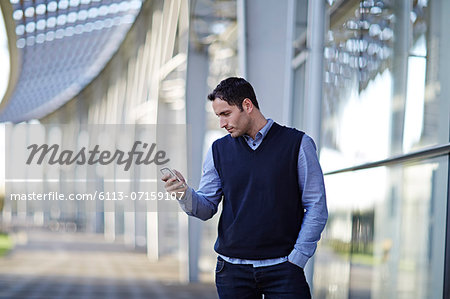 Businessman using cell phone outdoors Stock Photo - Premium Royalty-Free, Image code: 6113-07159107