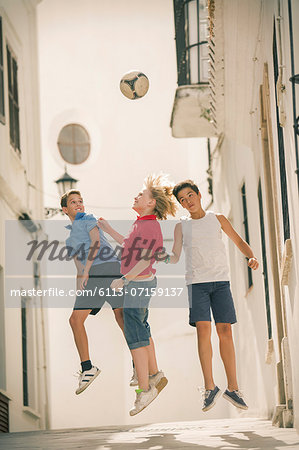 Children playing with soccer ball in alley Stock Photo - Premium Royalty-Free, Image code: 6113-07159137