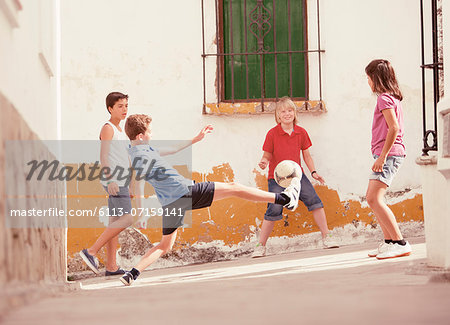 Children playing with soccer ball in alley Stock Photo - Premium Royalty-Free, Image code: 6113-07159141