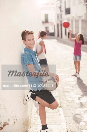 Boy holding soccer ball in alley Stock Photo - Premium Royalty-Free, Image code: 6113-07159145