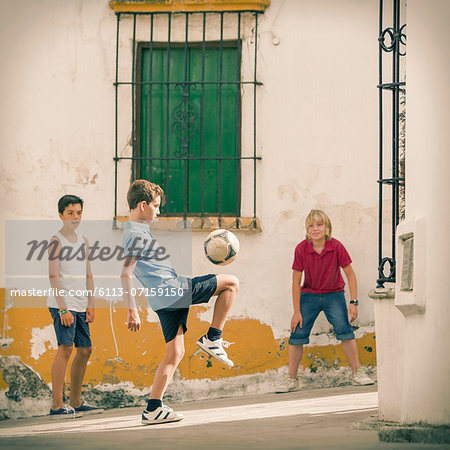 Children playing with soccer ball in alley Stock Photo - Premium Royalty-Free, Image code: 6113-07159150