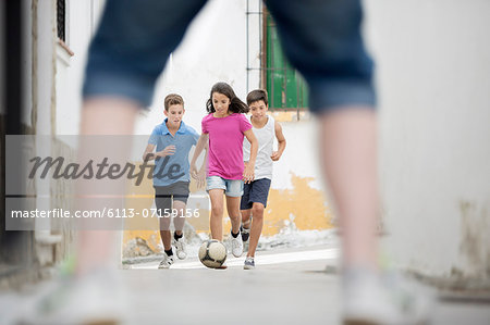 Children playing with soccer ball in alley Stock Photo - Premium Royalty-Free, Image code: 6113-07159156