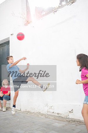 Children playing with soccer ball in alley Stock Photo - Premium Royalty-Free, Image code: 6113-07159159
