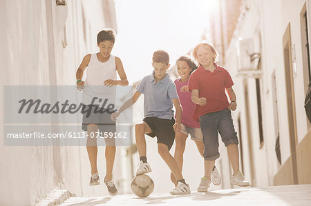 Children playing with soccer ball in alley Stock Photo - Premium Royalty-Free, Image code: 6113-07159162