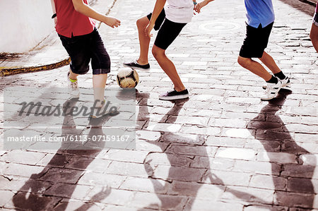 Children playing with soccer ball in alley Stock Photo - Premium Royalty-Free, Image code: 6113-07159167
