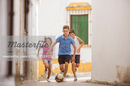 Children playing with soccer ball in alley Stock Photo - Premium Royalty-Free, Image code: 6113-07159172