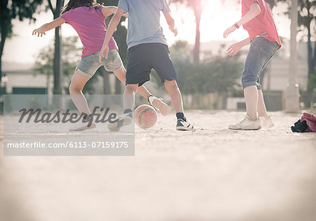 Children playing with soccer ball in sand Stock Photo - Premium Royalty-Free, Image code: 6113-07159175
