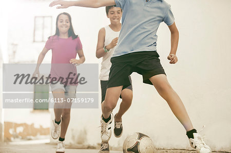 Children playing with soccer ball in alley Stock Photo - Premium Royalty-Free, Image code: 6113-07159179