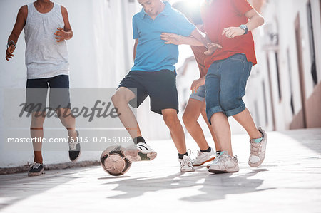 Children playing with soccer ball in alley Stock Photo - Premium Royalty-Free, Image code: 6113-07159182