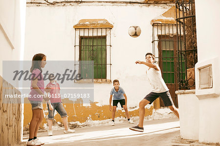 Children playing with soccer ball in alley Stock Photo - Premium Royalty-Free, Image code: 6113-07159183