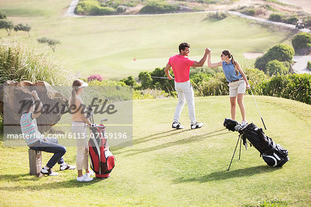 Friends playing golf on course Stock Photo - Premium Royalty-Free, Image code: 6113-07159196