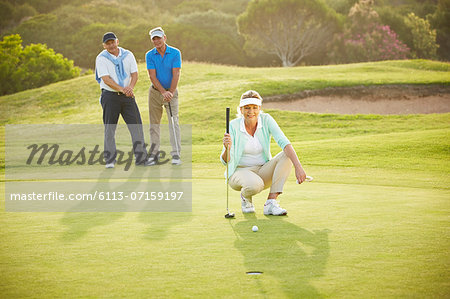 Senior friends playing golf on course Stock Photo - Premium Royalty-Free, Image code: 6113-07159197