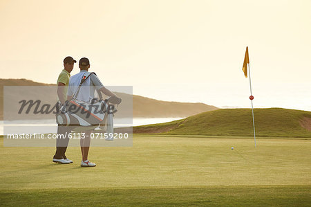 Men on golf course overlooking ocean Stock Photo - Premium Royalty-Free, Image code: 6113-07159200