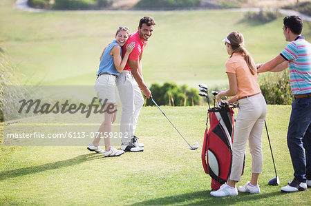 Friends laughing on golf course Stock Photo - Premium Royalty-Free, Image code: 6113-07159202