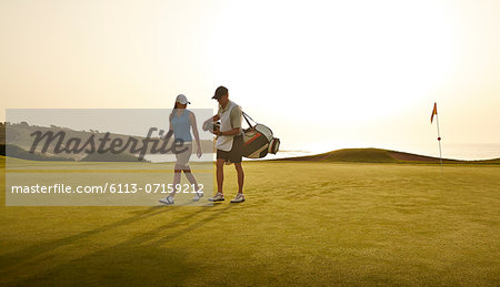 Caddy and woman walking on golf course overlooking ocean Stock Photo - Premium Royalty-Free, Image code: 6113-07159212
