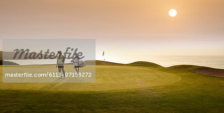 Golfer and caddy walking on golf course Stock Photo - Premium Royalty-Free, Image code: 6113-07159272