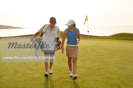 Golfer and caddy walking on golf course Stock Photo - Premium Royalty-Free, Image code: 6113-07159306